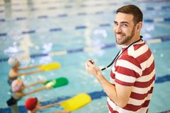 Swimming instructor with group. Portrait of smiling young swimming instructor training his group in the swimming pool stock photography