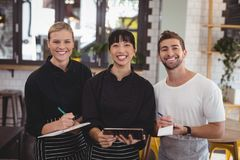Portrait of smiling young wait staff holding digital tablet with notepad and clipboard. At coffee shop Stock Photos