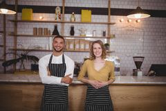 Portrait of smiling young wait staff standing against counter. At coffee shop Stock Image