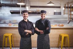 Portrait of smiling young wait staff in standing with arms crossed at coffee shop. Portrait of smiling young wait staff in standing with arms crossed against Royalty Free Stock Photography