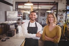 Portrait of smiling young wait staff standing with arms crossed by counter. In coffee shop Royalty Free Stock Photography