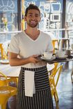 Portrait of waiter holding tray in cafe. Portrait of smiling young waiter holding tray in cafe Royalty Free Stock Photography