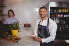 Portrait of smiling young waiter using digital tablet while standing by counter Stock Photos