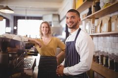 Portrait of smiling young waiter and waitress standing by espresso maker Stock Images