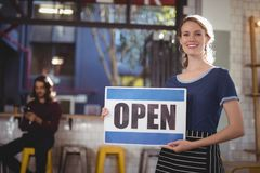 Portrait of smiling young waitress holding open sign placard Stock Photos