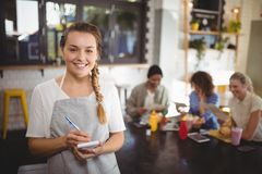 Portrait of smiling young waitress with notepad at cafe. Portrait of smiling young waitress with notepad standing at cafe Stock Photos