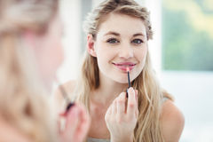 Portrait of smiling young woman applying lip gloss Stock Photography