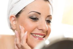 Portrait of smiling young woman applying moisturizing cream Royalty Free Stock Photography