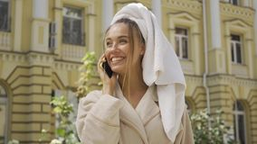 Portrait of cute smiling jou young woman in bathrobe with towel on head talking by cellphone on the street. Confident. Portrait smiling young woman in bathrobe stock video footage
