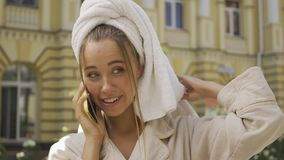 Portrait of cute smiling young woman in bathrobe with towel on head talking by cellphone on the street. Confident girl. Portrait smiling young woman in bathrobe stock video