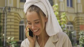 Portrait smiling young woman in bathrobe with towel on head talking by cellphone on the street. Confident girl enjoying. A beautiful day in the city chatting stock video footage