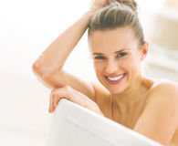Young woman in bathtub. Portrait of smiling young woman in bathtub royalty free stock photography