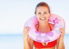 Portrait of smiling young woman on beach with swim ring Stock Image