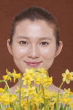 Portrait of smiling young woman behind a bunch of yellow flowers, studio shots Stock Photos