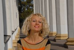 A portrait of a smiling and cheerful young woman with a blond curly hair, standing in the park. A portrait of a smiling young woman with a blond curly hair. The Royalty Free Stock Photo