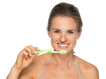 Portrait of smiling young woman brushing teeth Stock Photo