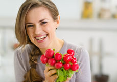 Portrait of smiling young woman with bunch of radishes Royalty Free Stock Images