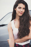 Portrait of a smiling young woman with car in background. Royalty Free Stock Photo