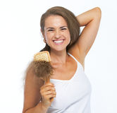 Portrait of smiling young woman combing hair Royalty Free Stock Images