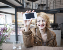 Portrait of smiling young woman displaying cell phone in cafe Royalty Free Stock Images
