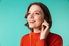 Portrait of a smiling young woman dressed in sweater. Listening to music in earphones isolated over blue background Stock Photos