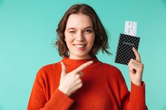 Portrait of a smiling young woman dressed in sweater. Pointing finger at a passport with flying tickets isolated over blue background Stock Photo