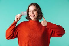 Portrait of a smiling young woman dressed in sweater. Holding credit card and showing thumbs up isolated over blue background Stock Images