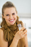 Portrait of smiling young woman drinking water in kitchen. High-resolution photo Stock Image