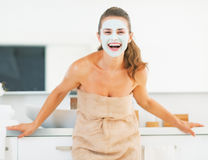 Portrait of smiling young woman with facial mask in bathroom Royalty Free Stock Photo
