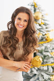 Portrait of smiling young woman in front of christmas tree Royalty Free Stock Photo