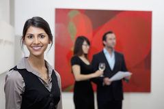 Portrait of smiling young woman in front of a couple in art gallery royalty free stock photography