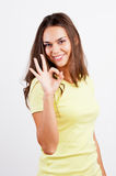 Portrait of smiling young woman gesturing okay Royalty Free Stock Image