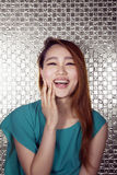 Portrait of smiling young woman with hand on her face with shiny background Stock Image