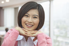 Portrait of Smiling Young Woman with Hands Under Her Chin, Looking At Camera royalty free stock image