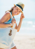 Portrait of smiling young woman in hat and with bag on beach Royalty Free Stock Image