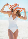 Portrait of smiling young woman in hat on beach Stock Photos