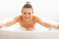 Portrait of smiling young woman having fun time in bathtub. Portrait of smiling young woman with brown hair having fun time in bathtub royalty free stock image