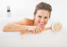 Portrait of smiling young woman holding body brush Stock Images