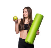 Portrait of smiling young woman holding rolled up exercise yoga mat and green apple isolated on white background. Royalty Free Stock Photos