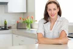 Portrait of a smiling young woman in kitchen Stock Images