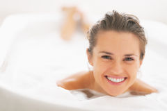 Portrait of smiling young woman laying in bathtub royalty free stock image