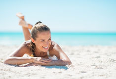 Portrait of smiling young woman laying on beach Stock Image