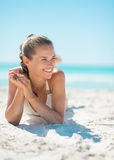 Portrait of smiling young woman laying on beach Stock Images