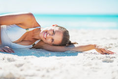 Portrait of smiling young woman laying on beach Royalty Free Stock Image
