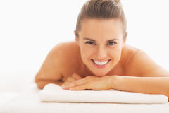 Portrait of smiling young woman laying on massage table Stock Photography