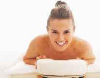 Portrait of smiling young woman laying on massage table Stock Photo