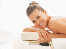 Portrait of smiling young woman laying on massage table Stock Photos