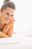 Portrait of smiling young woman laying on massage table Stock Image