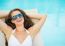 Portrait of smiling young woman laying on sunbed Royalty Free Stock Photos