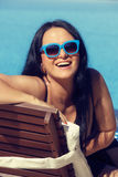 Portrait of smiling young woman laying on sunbed Stock Photos
